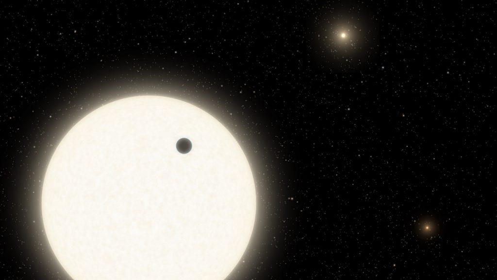 恒星の前を横切る系外惑星KOI-5Ab。右側に別の星も二つ描かれています。Credits: Caltech/R. Hurt (Infrared Processing and Analysis Center, or IPAC)